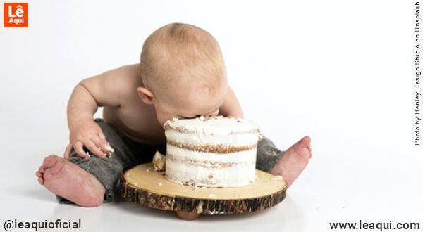 Bebê com o rosto enfiado em um grande bolo alertando para evitar obesidade infantil quarentena