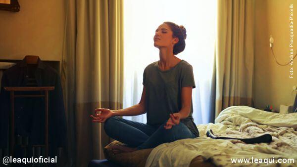 mulher meditando na posição de lótus em uma cama num quarto para Para aliviar a ansiedade