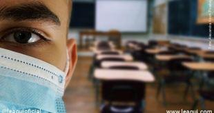 Rapaz com máscara cirúrgica tendo ao fundo uma sala de aula vazia reabrir escolas com segurança