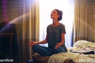 Mulher na posição de lótus em sua cama no quarto conquistar o autoconhecimento