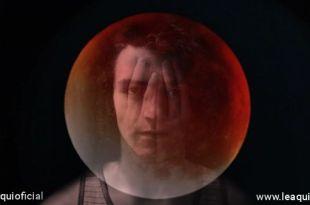 imagem de rapaz com as mãos semi transparentes cobrindo o rosto em meio à face escura da lua escondemos nossas emoções