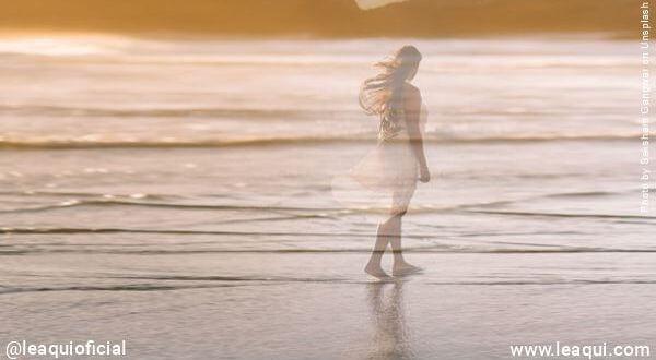 Espírito de uma mulher caminhando em uma praia morte na visão espírita
