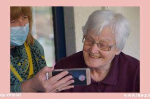 mulher com máscara cirúrgica mostrando algo em um telefone celular para uma senhora idosa cuidadores familiares