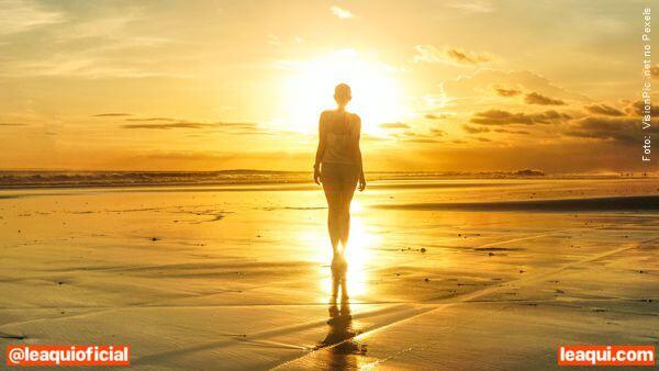 Mulher olhando o mar ao entardecer, indicando que podemos fazer um novo fim