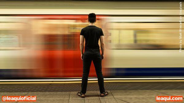 Homem parado vendo o trem passando à sua frente sua prosperidade