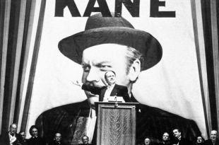 imagem do filme cidadão Kane com Kane discursando num púlpito com um grande cartaz dele atrás vida mais feliz