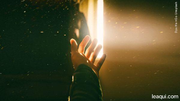 uma mão clamando pela luz que vem por uma fresta aflições