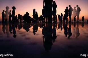 muitas pessoas na beira do mar em uma praia aguardando o novo amanhecer o amanhecer de uma era de amor boa convivência