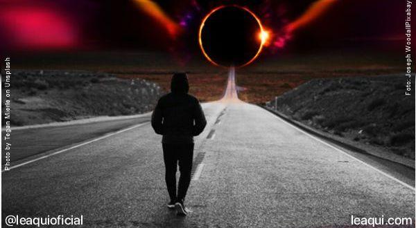 um homem de capuz com as mãos nos bolços caminhando em uma estrada vazia com um imenso eclipse no final da estrada esperanças ano por vir