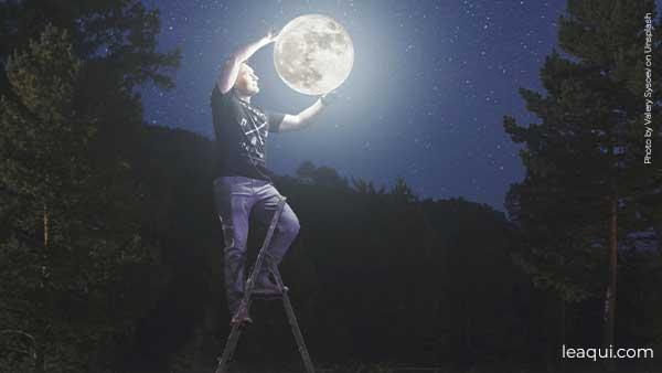 montagem fotográfica de um homem em uma escada trocando a lua como se ela fosse uma lâmpada 2021 o ano 1