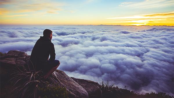 homem sentado no alto de uma montanha com ar contemplativo olhando para as nuvens que estão abaixo dele paciência provas da vida