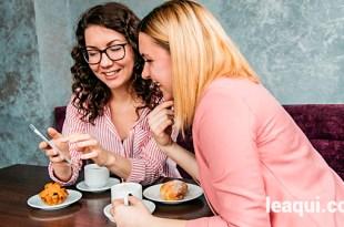 duas moças tomando café em uma mesa divertindo-se com o que estão vendo no telefone atitudes na vida
