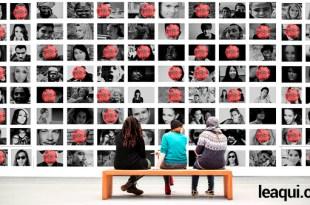 três pessoa sentadas em um banco olhando um enorme painel com fotos de pessoas e em algumas existe a imagem do vírus corona em vermelho descaso pandemia