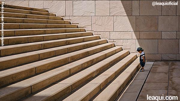 uma pequena criança , um pouco maior que um bebê para do frente a uma grande escada meditando para enfrentá-la problemas na vida