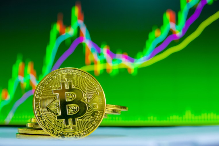 Bitcoin in front on green trading graph with red and green candels