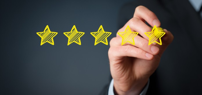 man in suit drawing a 5 star review with black background