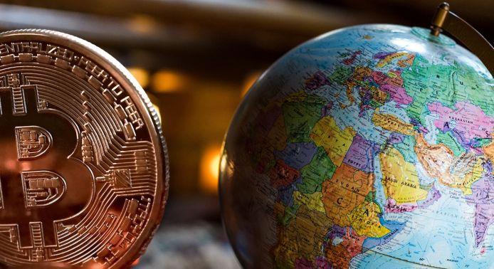 World map next to bitcoin with lights in the background
