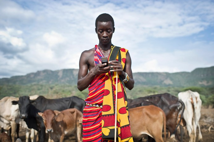 Isaac Mkalia, 20 years old, a teacher by profession is checking his mobile phone.