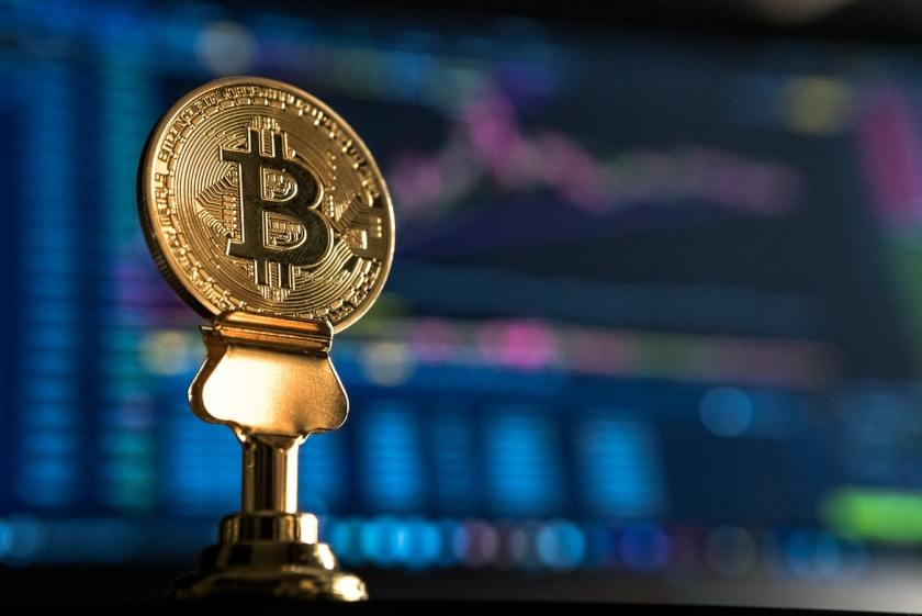 bitcoin coin on a pedestal in front of computer screen with trading graph