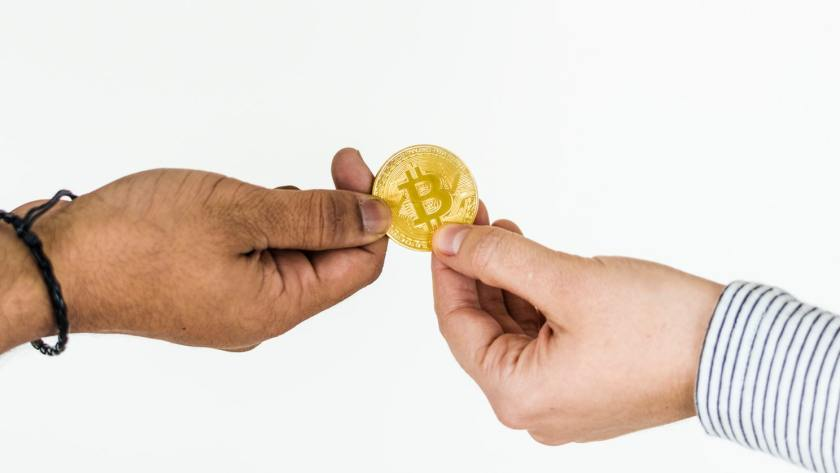 two people holding a bitcoin coin