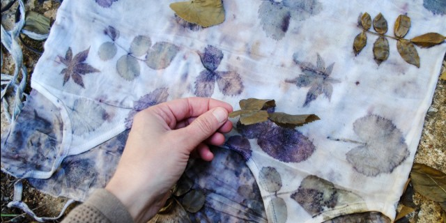 A hand lifting leaves off a cotton top to reveal the eco-prints underneath
