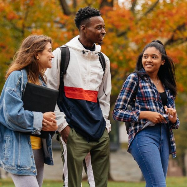 Group of students walking through college campus