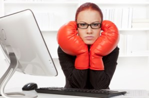 Agressive businesswoman with boxing gloves ready for fighting