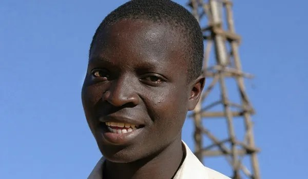 Photo of William Kamkwamba with windmill in the back