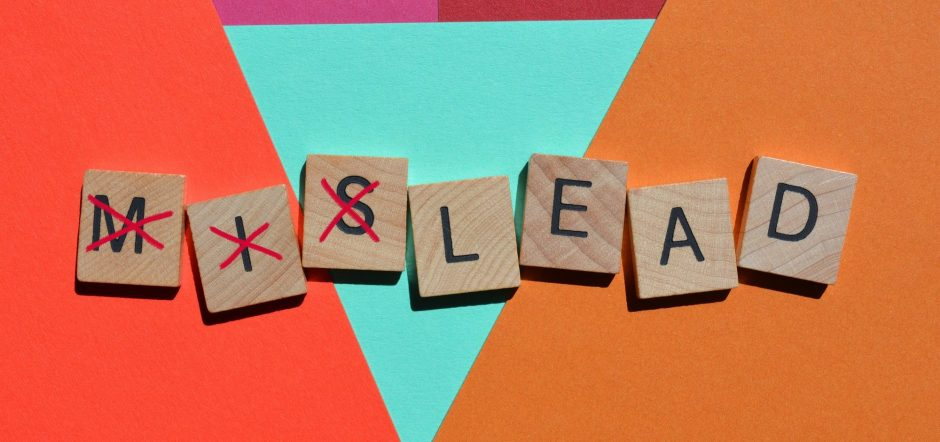 Mislead, word in 3D wooden alphabet letters with mis crossed out leaving the word lead.