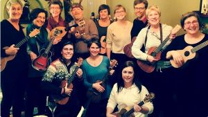 A group of women and men hold ukuleles and smile.