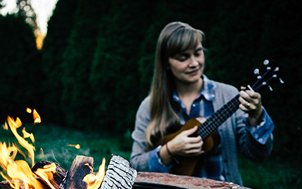 Avery sits next to a campfire and plays the ukulele at dusk.