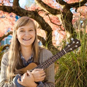 Photo of teacher Avery holding a ukulele and smiling in front of a tree with red leaves.