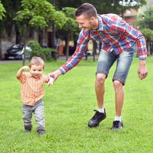 baby boy taking first steps with father help in a park