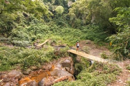 Walking on a bamboo bridge at Murunda 'o Muru waterfall