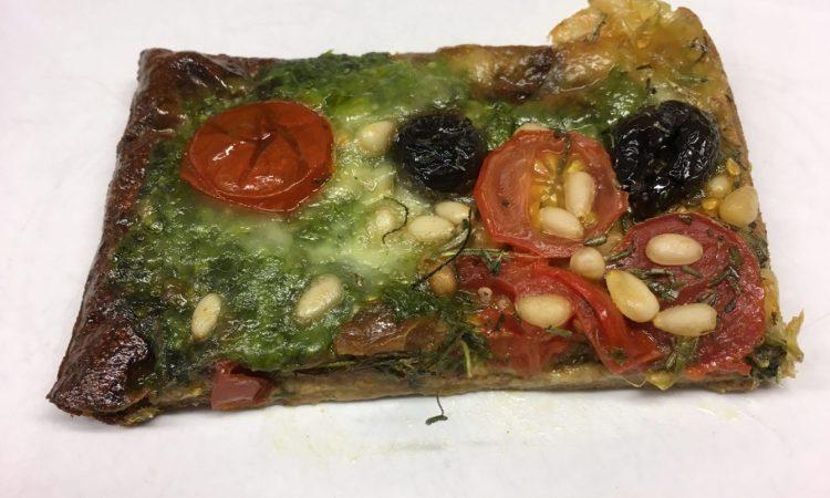 Pizza mit Pesto, Tomaten, Pinienkernen und Rucola