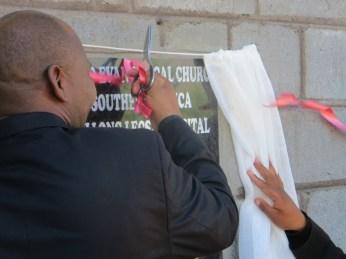 Rev. Masemene cuts the ribbon on new staff housing building
