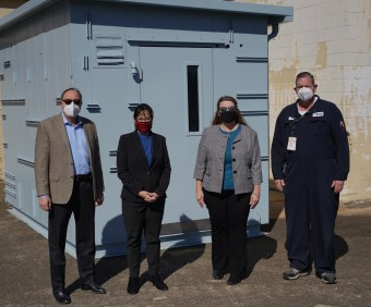 Four people standing in front of the analyzer shed. Robert Bradshaw, Site Manager, INEOS Olefins & Polymers Battleground Manufacturing Complex; Dr. Lynda Villanueva, President, Lee College; Marsha Tuha, Executive Director, Lee College Center for Workforce & Community Development; Dave Lierman, Maintenance Supervisor, INEOS Olefins & Polymers Battleground Manufacturing Complex.