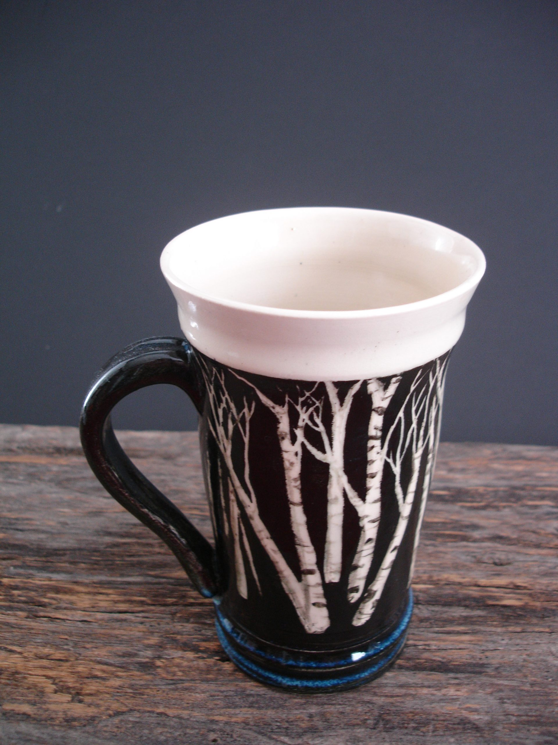 black cup with birch trees
