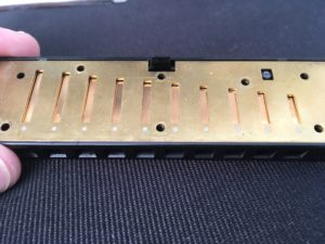 Harmonica with cover plates removed showing how the blow plate fits onto the comb