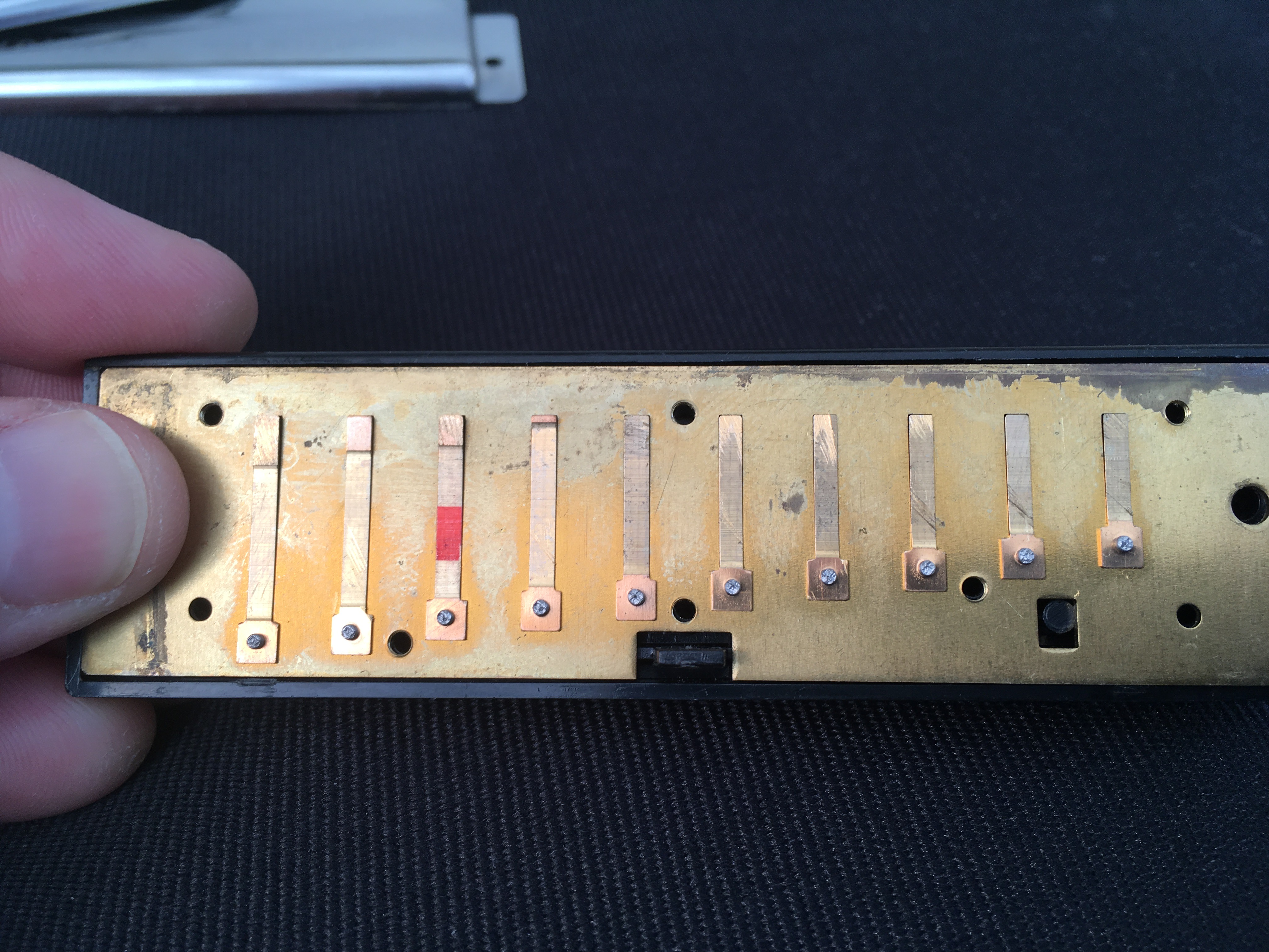Harmonica with cover plates removed showing the draw plate on the comb
