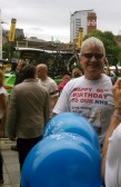 Leeds KONP member wearing Happy Birthday NHS tshirt, in front of one of the support bikes cars with multiple bikes on the roof