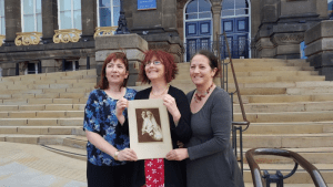 Harriet Stevens with sisters Jessica Russell and Rachel Stevens holding their grandparent's wedding photo outside Leeds City Museum.