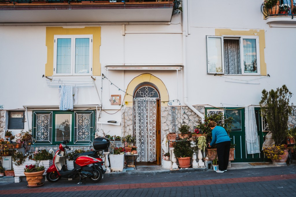 street photography italy woman caring for plants outside house italy