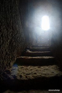 shadowy stairs carved into a stone tunnel leading up to a bright entranceway.