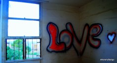 "the word ""LOVE"" written in bubble letters with spray-paint on two walls. the ""v"" is divided in half by the corner seem where the wall joints the other."