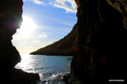 Looking through a large natural archway in the rocks out at a bay, the sun, the sky.