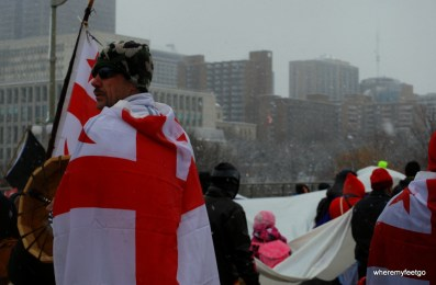 man wearing a camouflage toque and a white flag with a red cross on it. he has a drum in his hand and is looking out behind him at the marchers filing down the street.