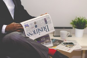 Photo of man reading business section of newspaper.