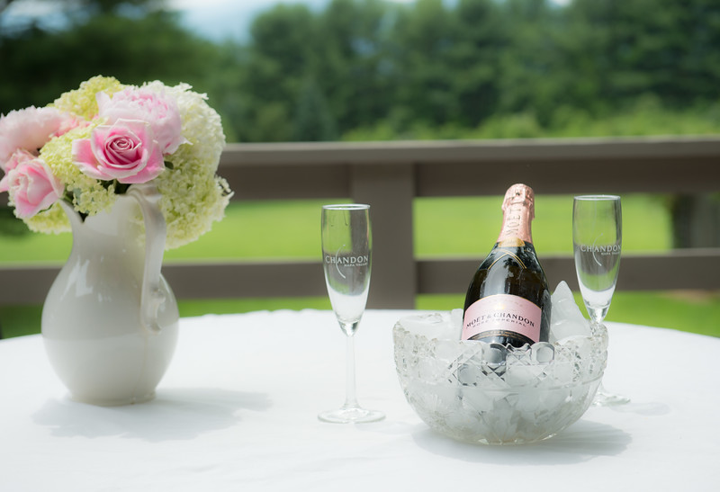 Photo of champagne in ice bucket and flower
