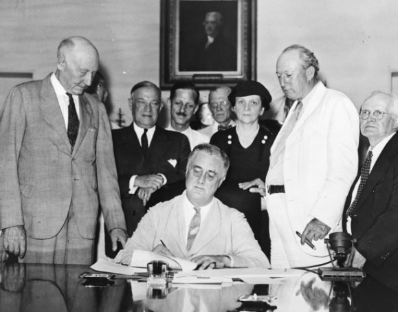 President Franklin D. Roosevelt signs the Social Security Act in 1935.